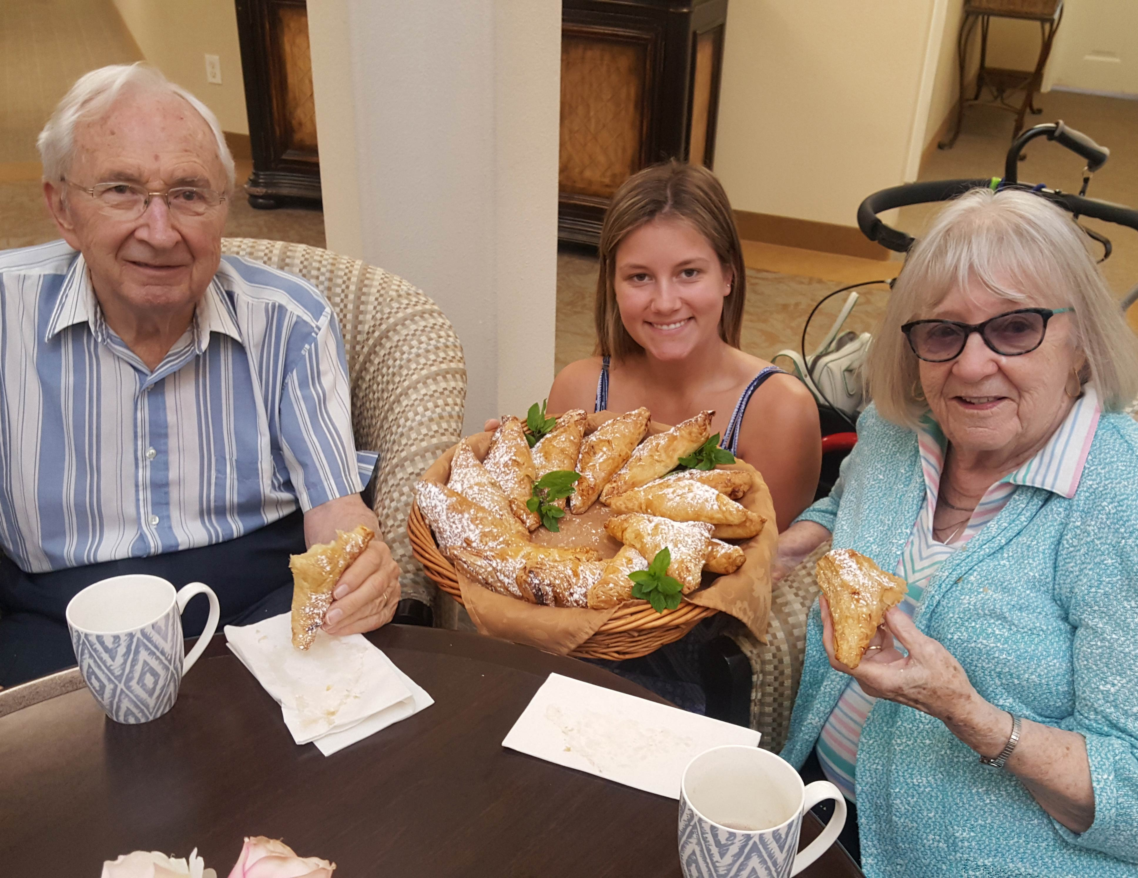 Two seniors and a volunteer holding baked goods.