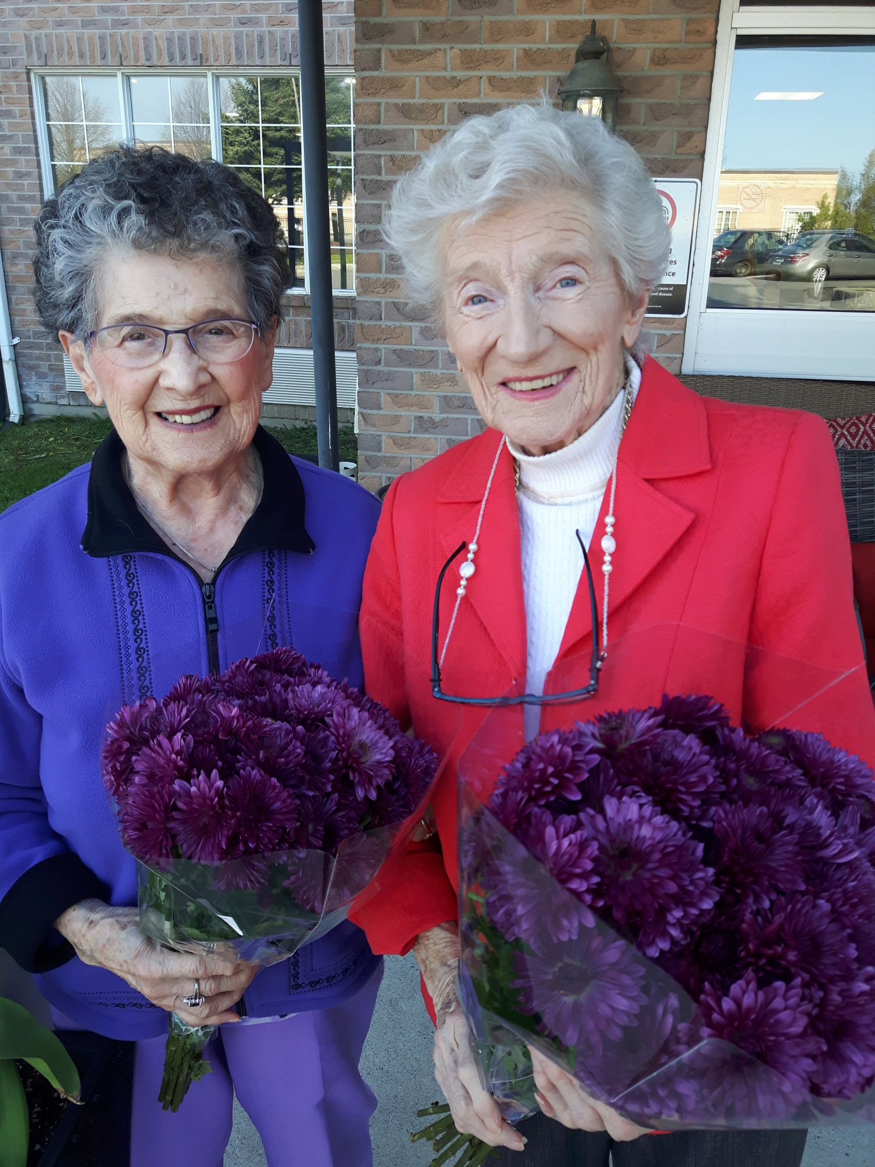 Two ladies holding bouquets of flowers.