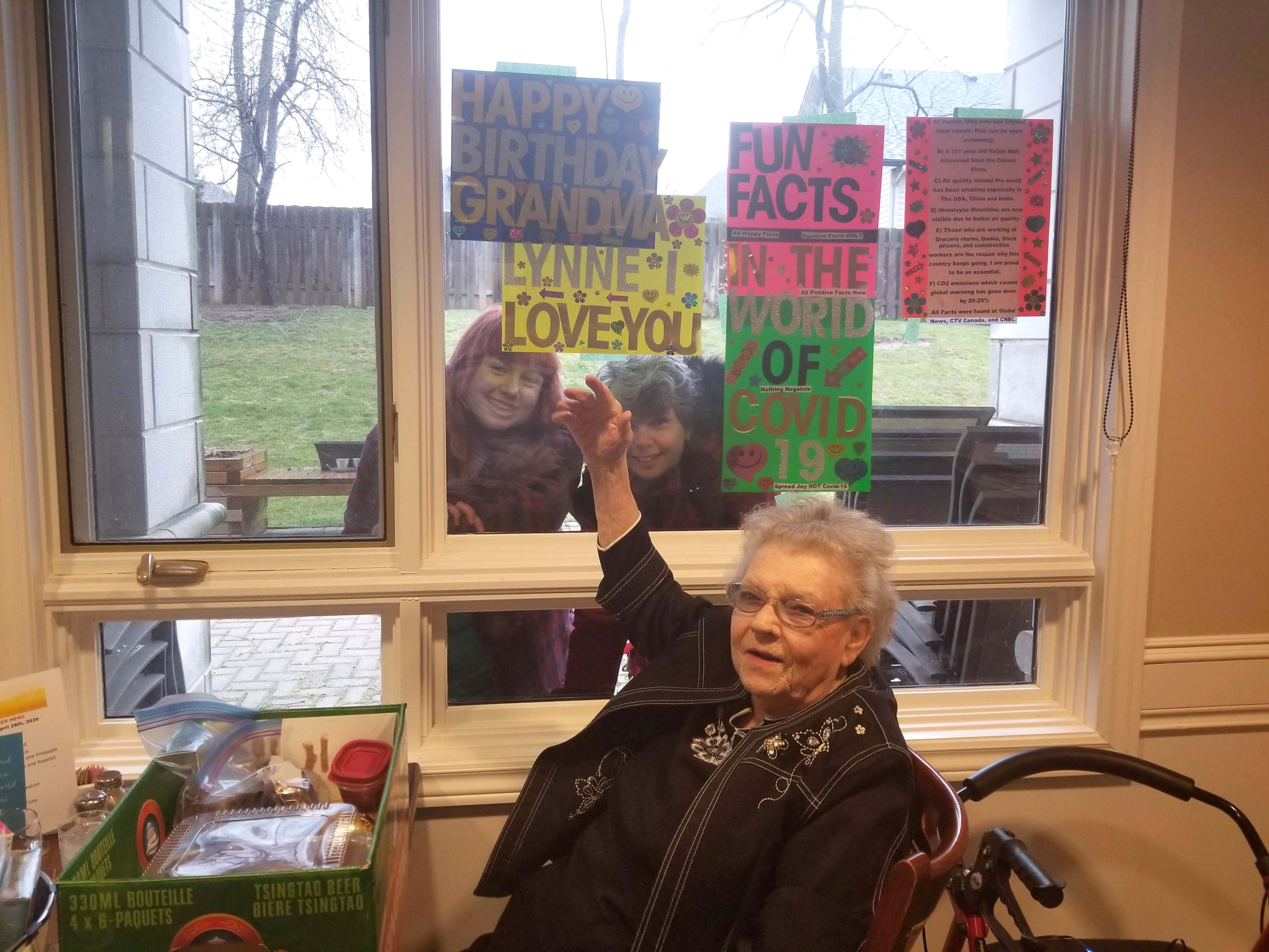 A resident having a window visit with her family to celebrate her birthday.