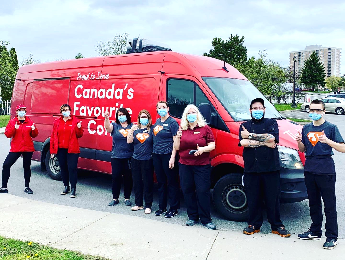 Team members standing in front of a van.