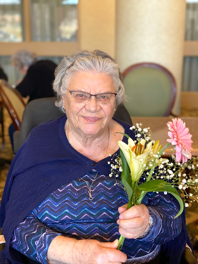 A resident holding a bouquet of flowers.