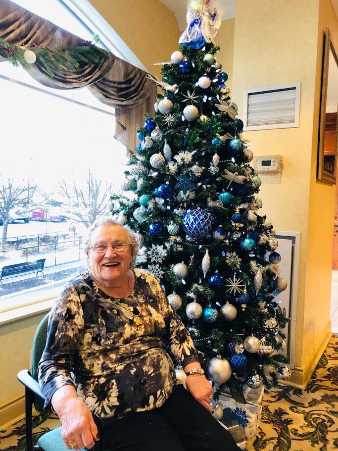 A resident enjoying the holidays in front of a Christmas Tree.