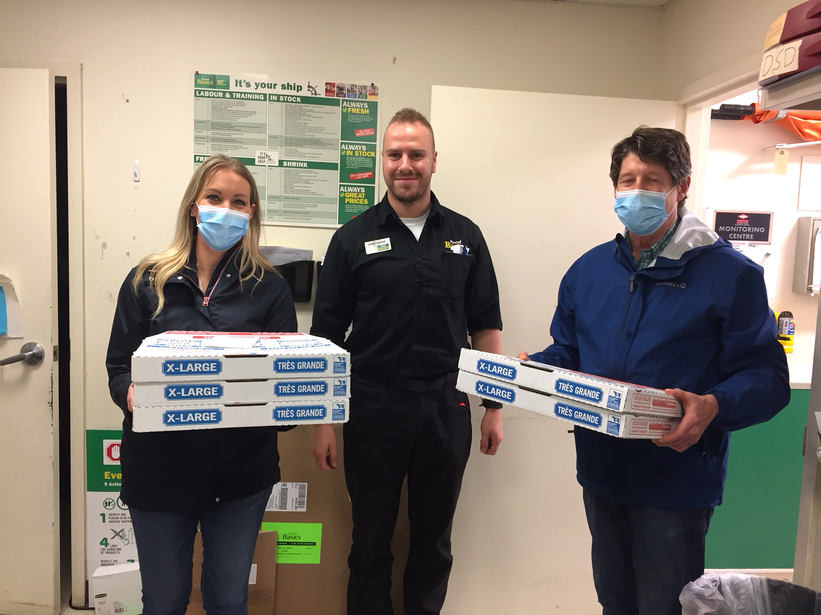 Team members with boxes of pizza donated from Domino's Pizza.
