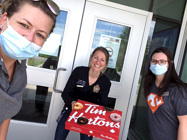 Team members holding Tim Horton's donuts.