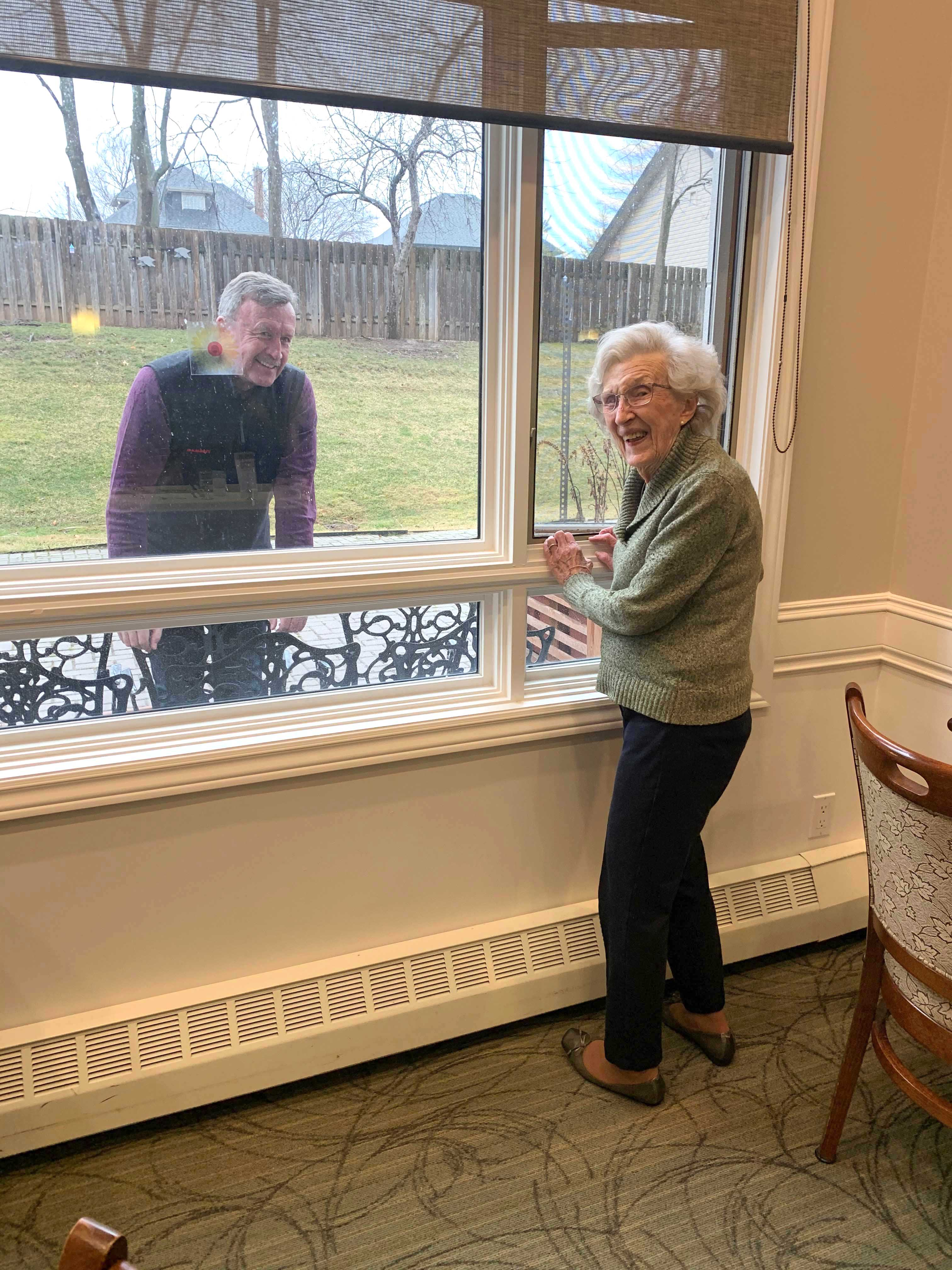 A resident having a window visit with a family member.