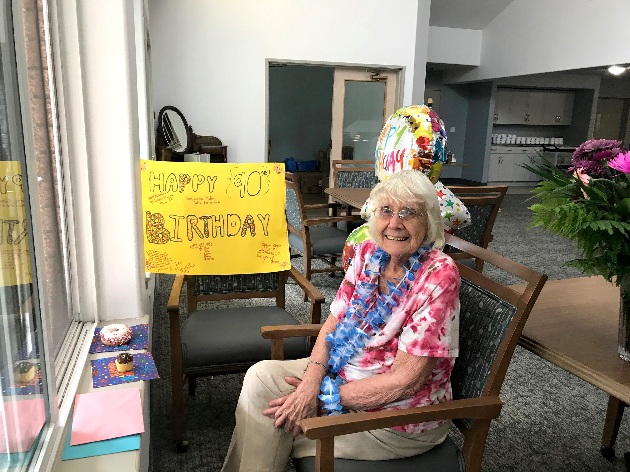 A resident celebrating her 90th birthday with window visits from her family.