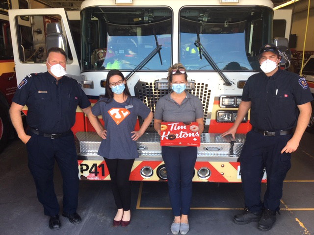 Team members and local firefights holding Tim Horton's donuts.