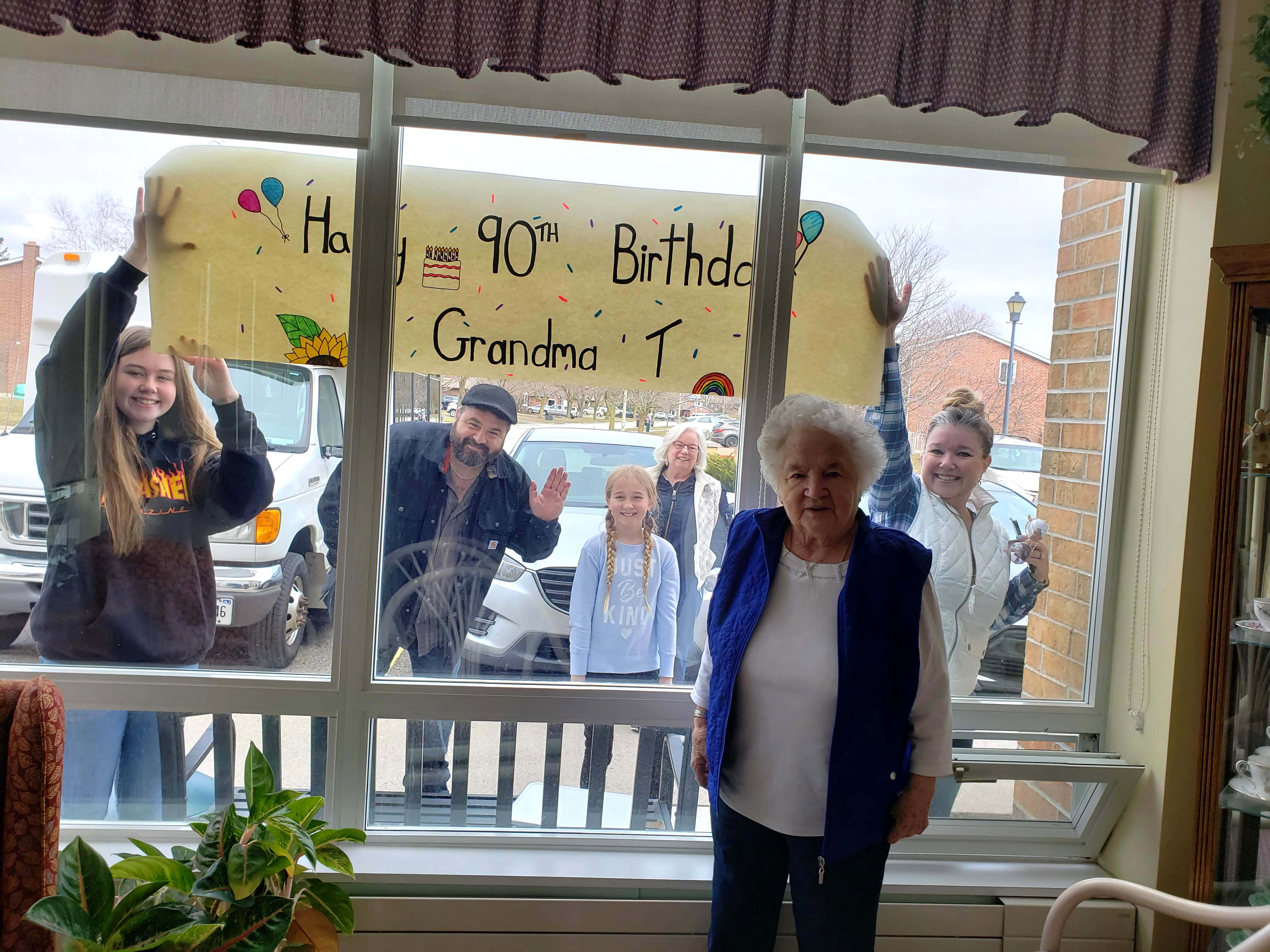 A resident family posing outdoors for a photo together to celebrate resident's 90th birthday.