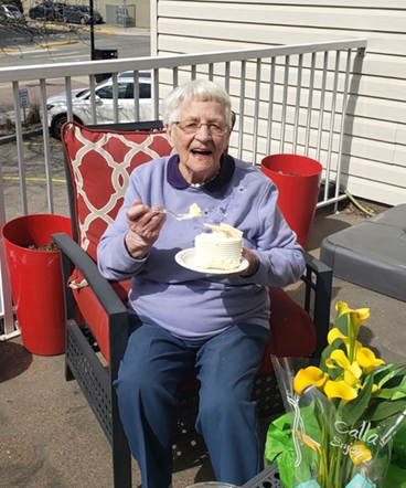 A resident on her balcony eating cake to celebrate her birthday.