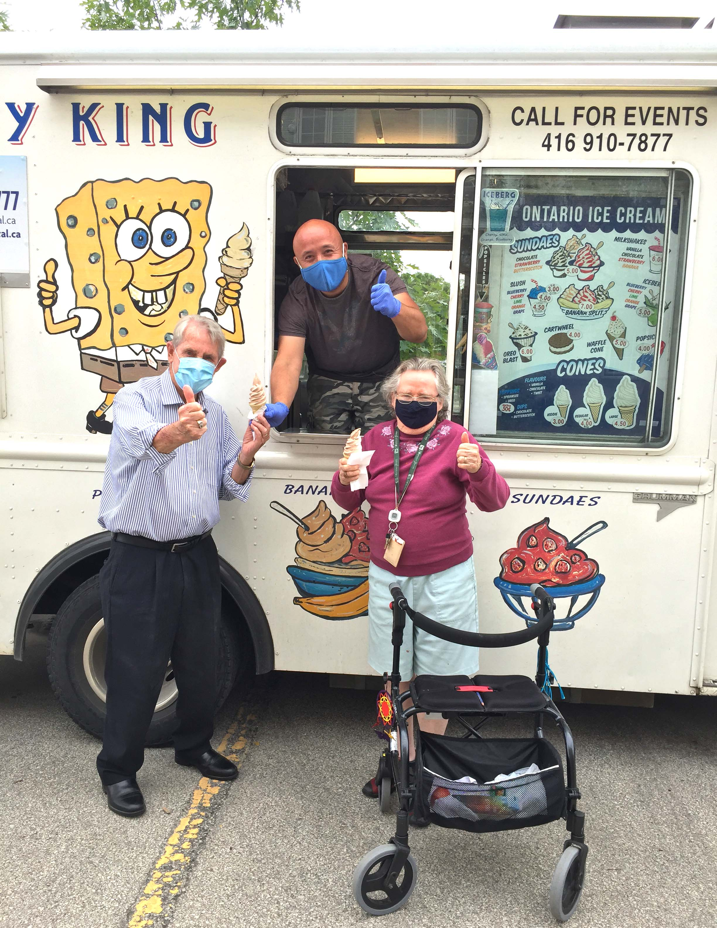 A lady and gentleman receiving ice cream cones from a male employee in an ice cream truck.