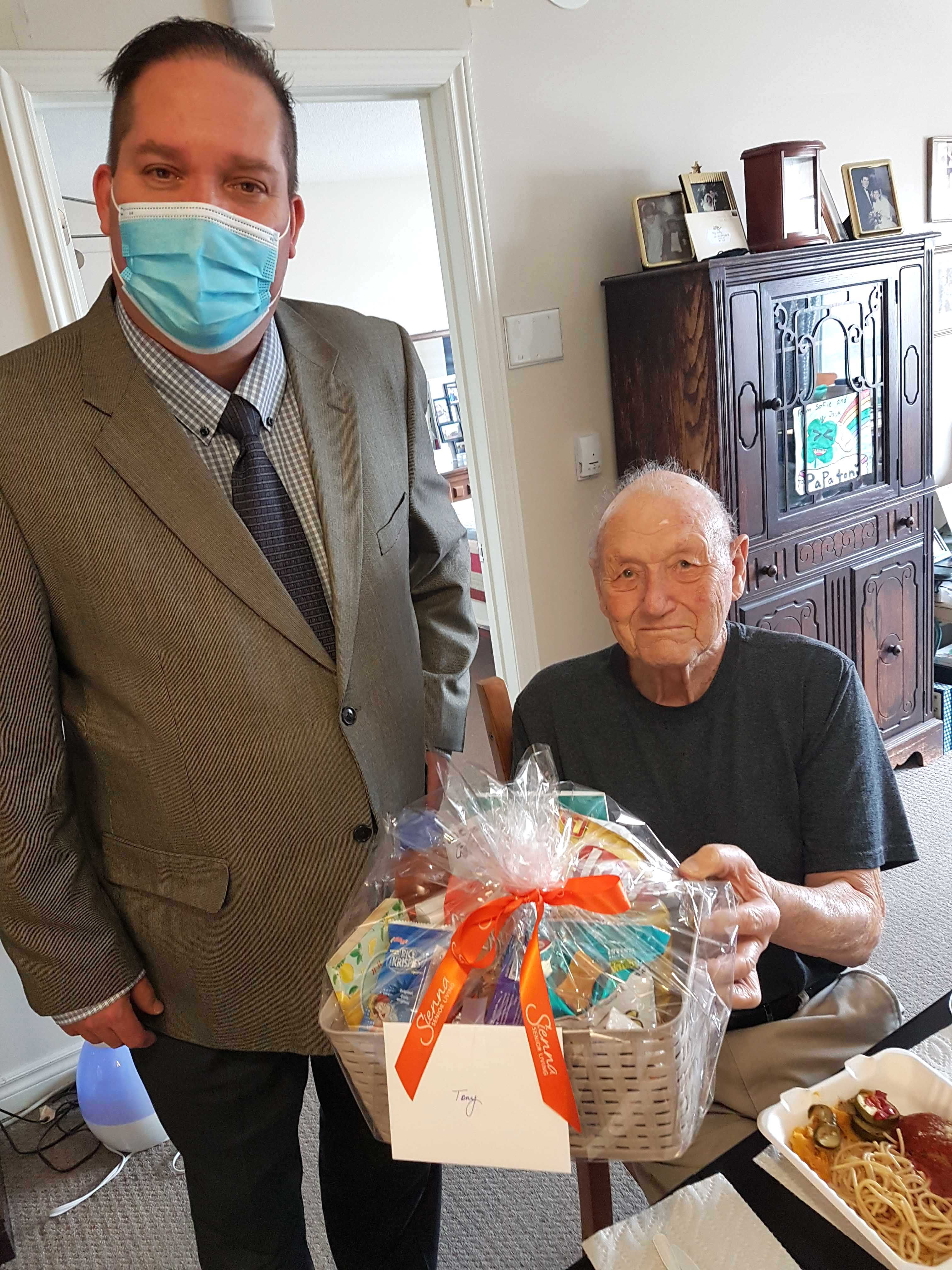 A resident and team member holding a gift basket.