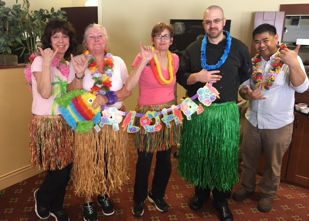 Team members dressed up for a Hawaiian luau.