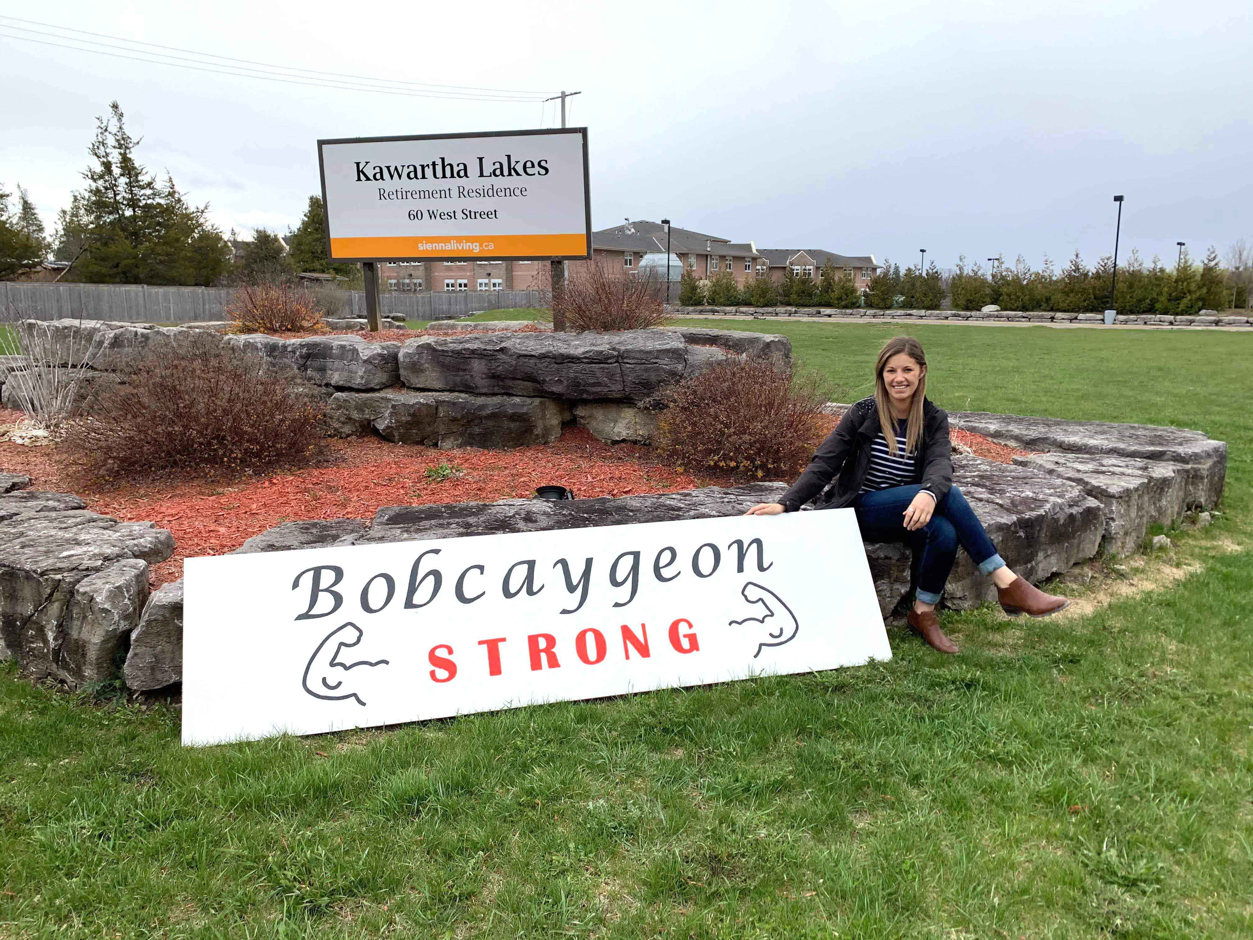 "A team member posing with a sign that says ""Bobcaygeon Strong""."