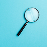 Magnifying glass on blue background.