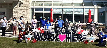 group photo of team members standing behind the Heroes signage at the front entrance of Quinte Gardens