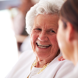 image of a female senior smiling towards a female caregiver.