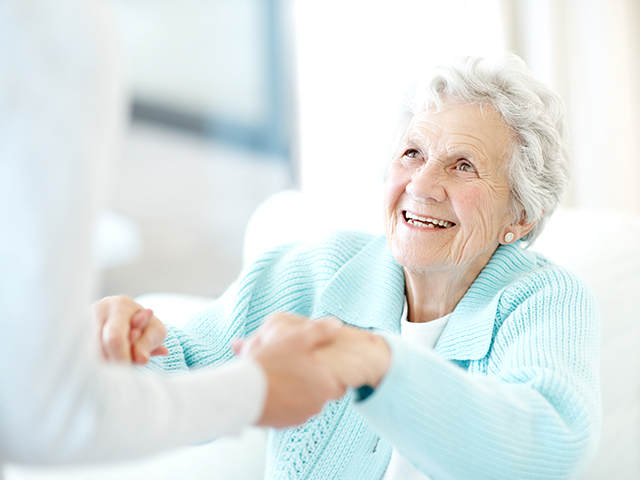 image of a happy female senior reaching out her hands to her caregiver.