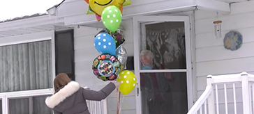 a female team member from Waterford Barrie delivering a bouquet of balloons to a senior