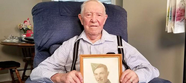 image of Gilbert sitting on a sofa while holding a photo of himself in uniform.