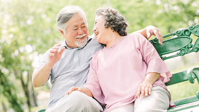 image of an Asian senior couple siting on a green bench in the park while laughing together