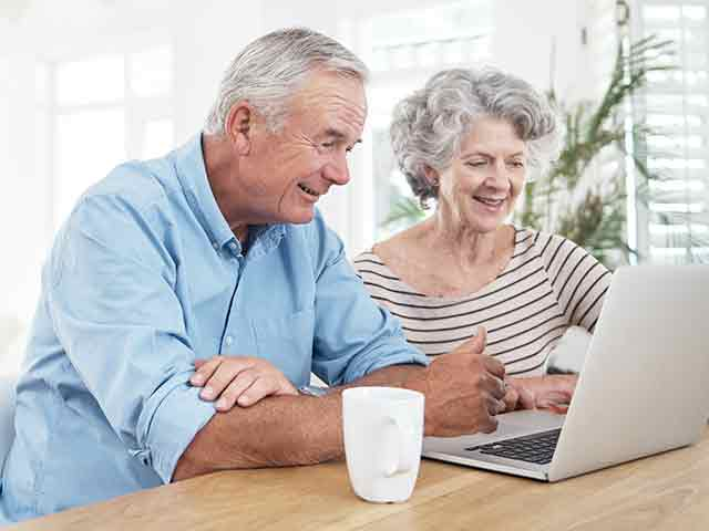 image of a senior couple using a laptop at home