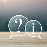Question mark and information chat icon on wooden table over cityscape at sunset