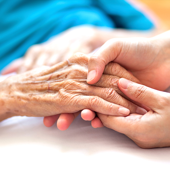 photo of a caregiver's hand is holding a senior's hand gently.