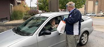 Eric Foster hands out an Orchard Valley Retirement Thanksgiving dinner to Pam Phillips (photo: Vernon Matters)