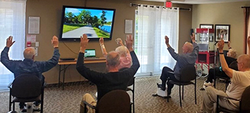 Residents at Cedarvale Lodge Retirement and Care Community in Georgina virtually cycle through Road Worlds for Seniors.