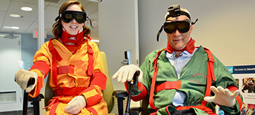 image of Brian Richardson, Chief Marketing Officer and Amanda Paterson, a team member from Sienna experiencing an aging-simulation.
