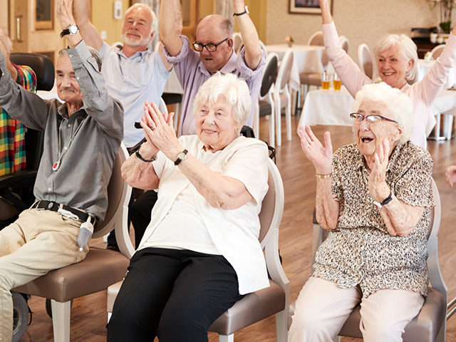 image of a group of seniors smiling together while in a retirement home