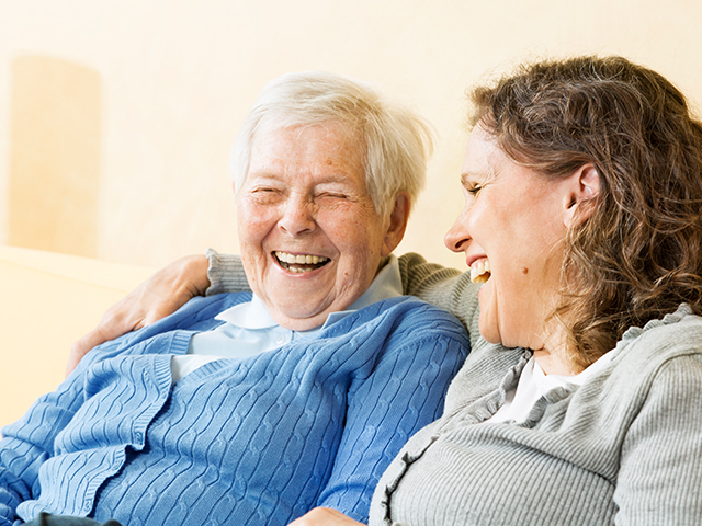 image of senior woman and mature woman/caregivier, sitting on sofa and laughing together