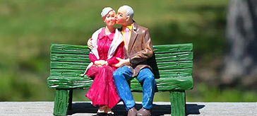 image of a senior couple doll sitting on a green bench in an outdoor setting.