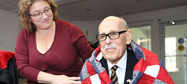 U.S. Army veteran William Moss, 89, receives a U.S. Quilt of Valor from Anna Donatucci during a ceremony at Windsor's Kensington Court Retirement Residence on Friday.