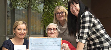 image of Mariposa Gardens resident Irene Neely (second from left), Miriam Landry, executive director (third from left), and Jannine Rennie, director of resident programs (right), presented a cheque
