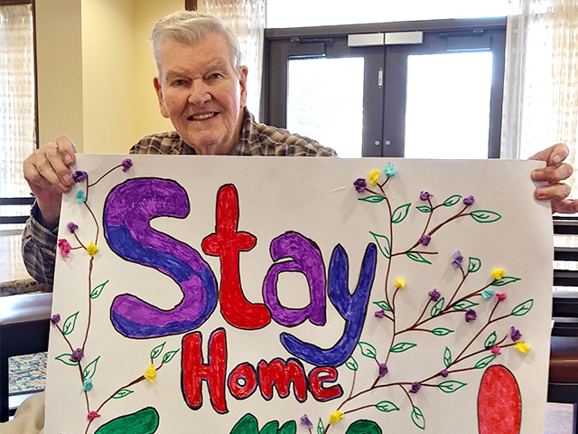 "picture of a male resident holding up a sign saying ""Stay Home for us!"""