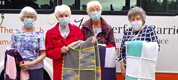 Four female members of the knitting group at Waterford Barrie Retirement Residence, showcase four of the afghans they generously donated and delivered to Hospice Simcoe.