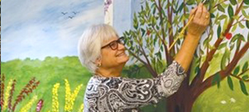 image of a resident of Victoria Manor is drawing on the wall mural