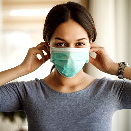 image of a female caregiver putting up her mask confidently
