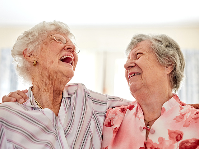 image of two happy elderly women embracing each other at home