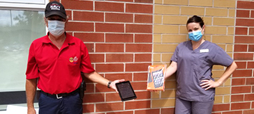 Orillia Rotarian Michel Rousseau presents tablets to Sarah Galbraith of Spencer House.