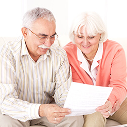 image of a senior couple reading at a piece a paper and smiling together