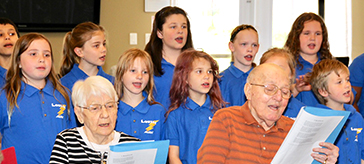 photo of the seniors of Cedarvale Lodge singing together with the students from the publish school